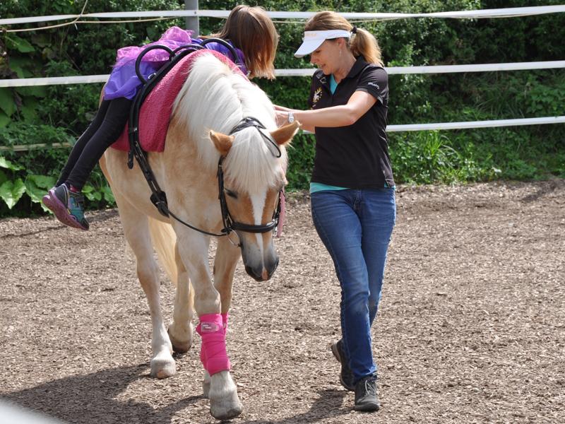Voltigierübung in der Förderung mit dem Pferd